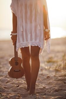 Mulher músico com ukulele na praia, férias de verão