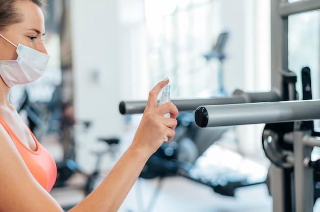 Mulher na academia com máscara médica, desinfetando equipamentos de ginástica