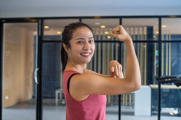 Mulher na academia estica os músculos, mostra força, boa saúde e sorri na academia. exercite o conceito saudável
