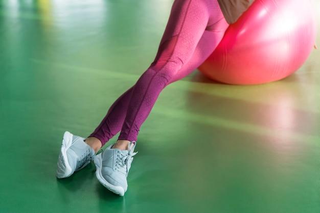 Mulher na academia fazendo exercícios com bola de pilates
