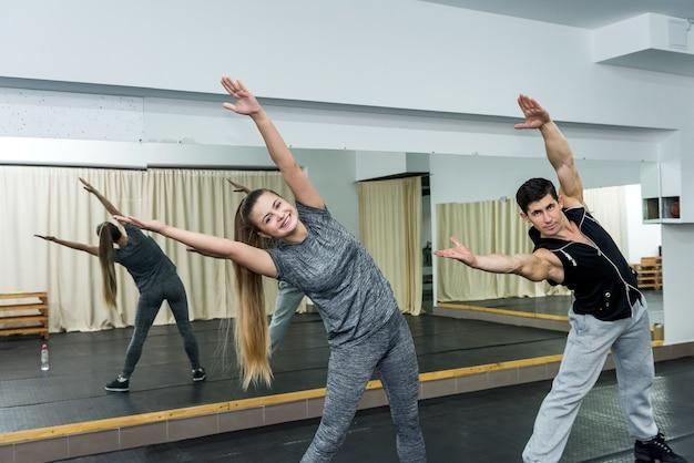 Mulher na academia fazendo exercícios com o instrutor