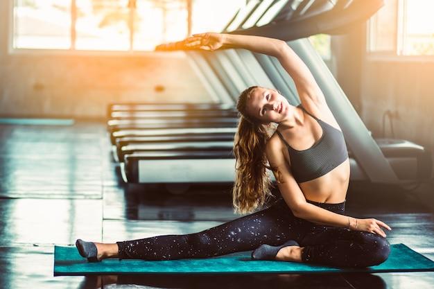 Mulher na academia fazendo exercícios de alongamento e sorrindo no chão