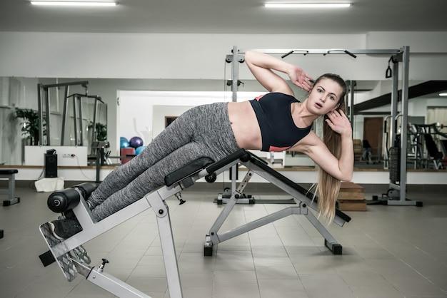 Mulher na academia fazendo exercícios para a imprensa