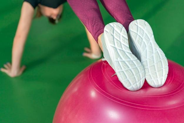 Mulher na academia fazendo prancha com bola de pilates