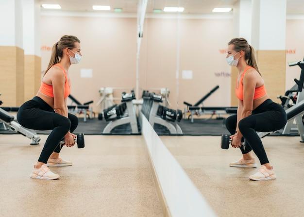 Mulher na academia treinando com máscara médica na frente do espelho