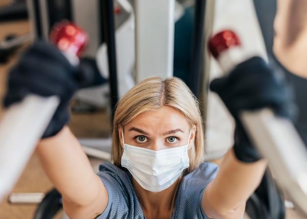 Mulher na academia usando equipamento com máscara