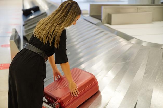 Mulher na área de retirada de bagagem