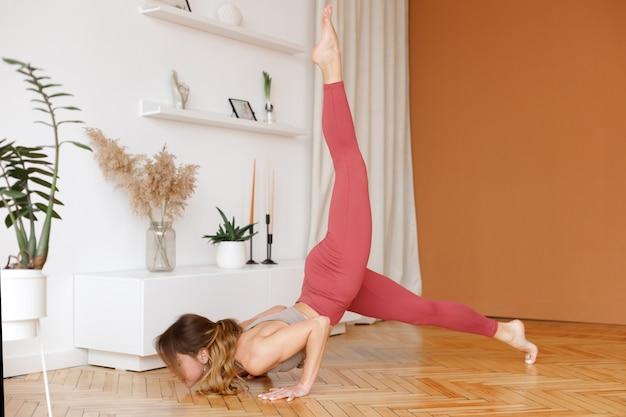 Mulher na barra de ioga ioga em casa