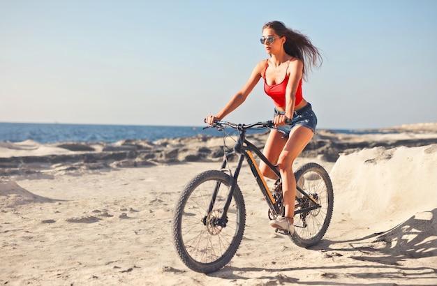 Mulher na bicicleta na praia