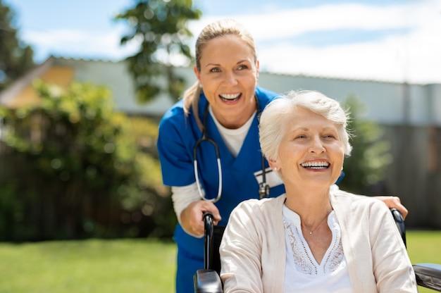 Mulher na cadeira de rodas se divertindo com enfermeira