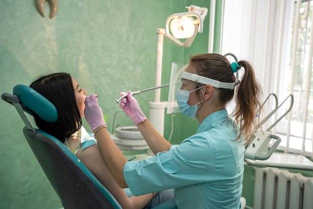 Mulher na cadeira do dentista tratando o dente sem dor