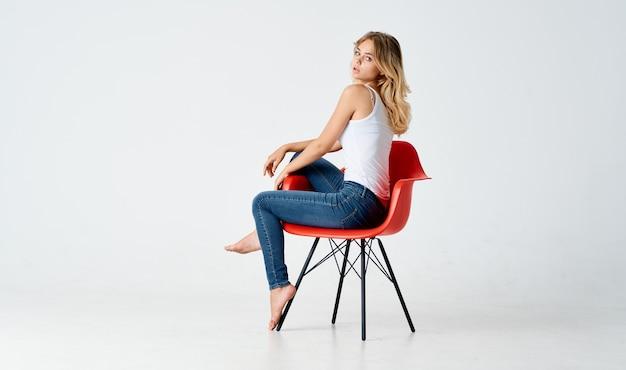 Mulher na cadeira vermelha posando glamour, estilo de vida, moda