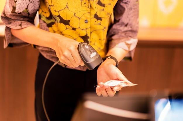 Mulher na caixa registradora, digitalização de código de barras de uma etiqueta