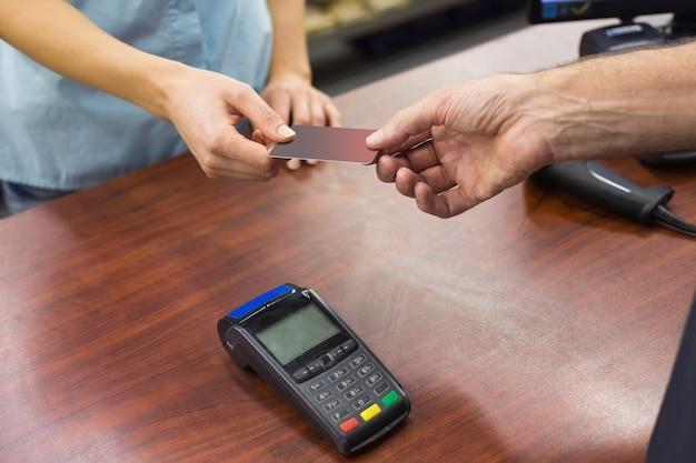 Mulher na caixa registradora que paga com cartão de crédito