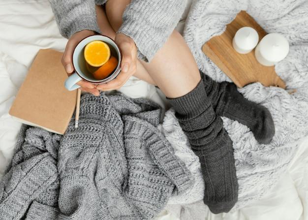 Mulher na cama bebendo chá