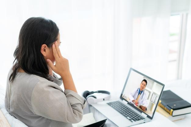 Mulher na cama branca falando com o médico usando tecnologia da tele saúde