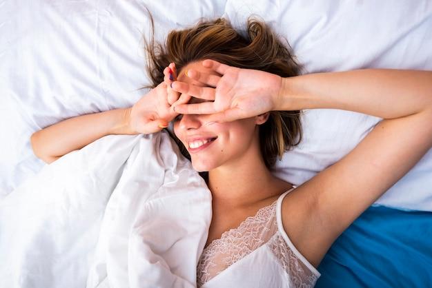 Mulher na cama, cobrindo os olhos