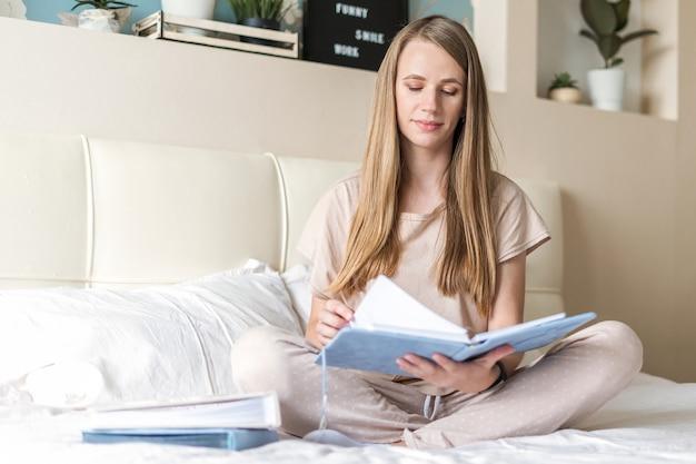 Mulher na cama com cadernos