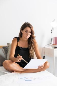 Mulher na cama com caneta e papéis