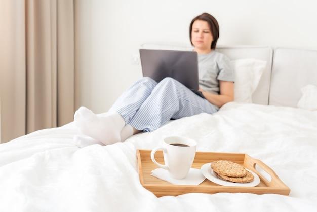 Mulher na cama com laptop e café da manhã