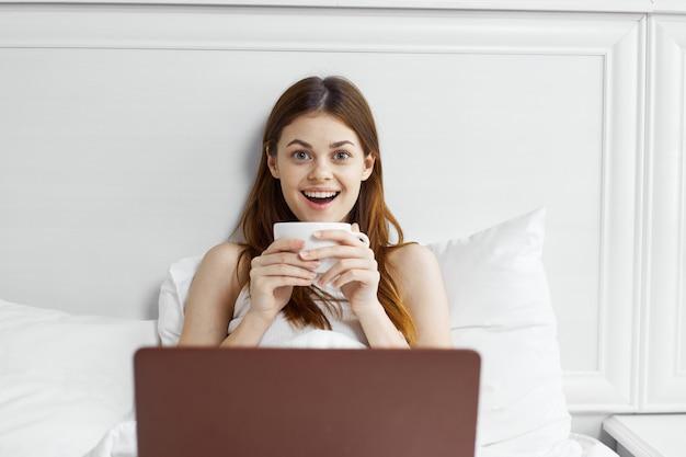 Mulher na cama com uma caneca de café e laptop