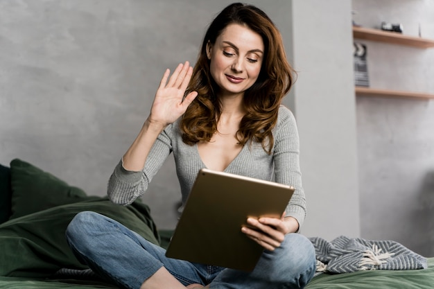 Mulher na cama fazendo streaming com tablet