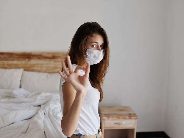 Mulher na cama, máscara médica gesticulando com a mão