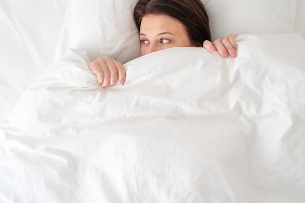 Mulher na cama, olhando surpreso debaixo do cobertor