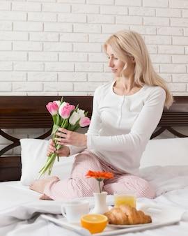 Mulher na cama surpreendida com café da manhã