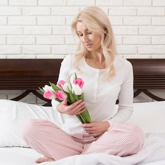 Mulher na cama surpreendida com flores
