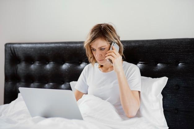 Mulher na cama usando laptop e celular