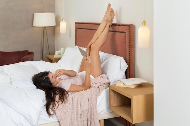 Mulher na cama usando tablet