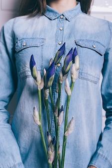 Mulher na camisa jeans segurando um buquê de íris azuis, enquadramento vertical