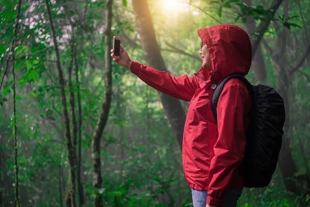 Mulher na capa de chuva vermelha fotografando com telefone móvel, natureza feliz