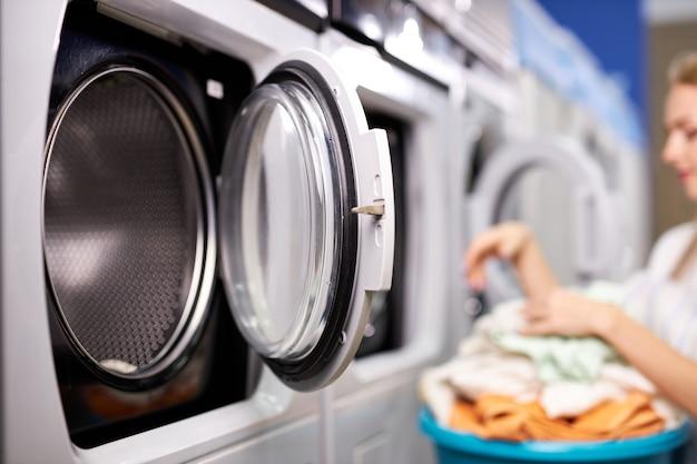 Mulher na casa de lavagem, separando roupas limpas, fazendo tarefas domésticas, mulher tira roupas da máquina de lavar, segurando a bacia. foco na máquina de lavar
