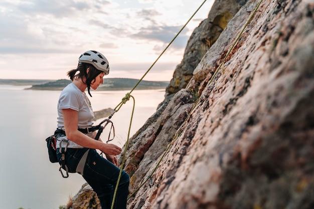 Mulher na casa dos 30 anos descendo uma montanha enquanto escala