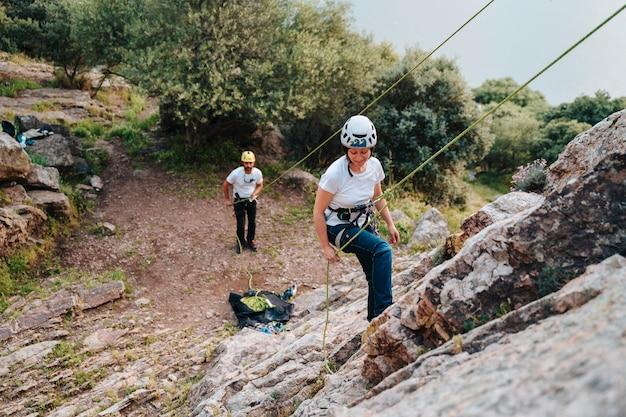 Mulher na casa dos 30 anos descendo uma montanha enquanto o parceiro a ajuda