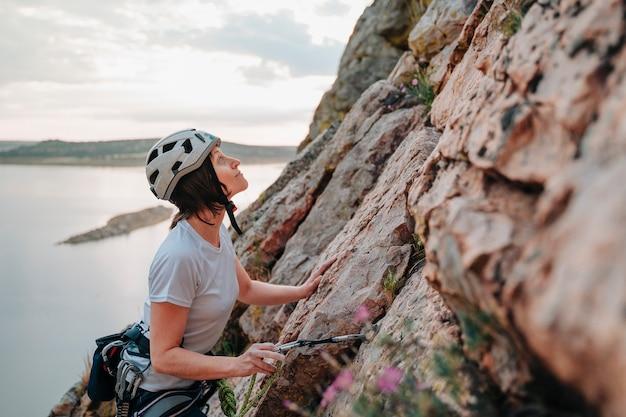 Mulher na casa dos 30 anos escalando uma montanha enquanto olha o pôr do sol