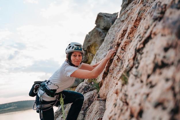 Mulher na casa dos 30 anos escalando uma montanha enquanto olha para a câmera