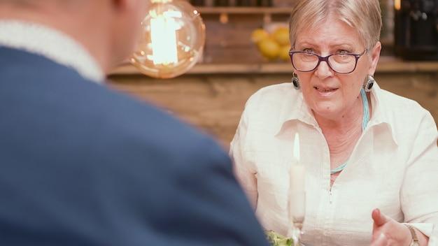 Mulher na casa dos sessenta anos contando ao marido uma história interessante durante as refeições em um restaurante. casal conversando. casal relaxado. dois aposentados.