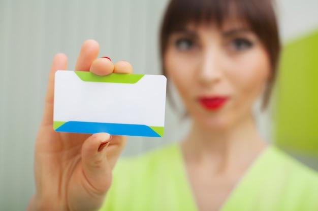 Mulher na clínica dentária segurando um cartão de visita em branco