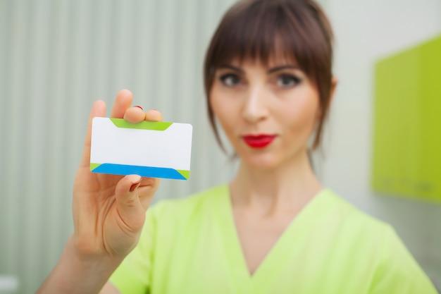 Mulher na clínica odontológica segurando cartões de visita em branco