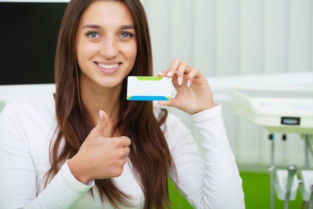 Mulher na clínica odontológica, segurando o cartão de visita em branco