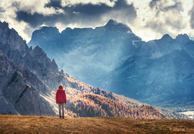 Mulher na colina está olhando para as montanhas majestosas ao pôr do sol