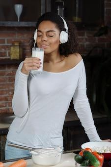 Mulher na cozinha com cheiro de leite Foto gratuita