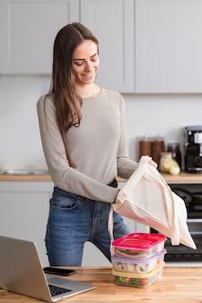 Mulher na cozinha com comida e computador portátil