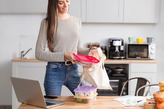 Mulher na cozinha com laptop e comida