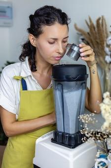 Mulher na cozinha com processo de fabricação de pudim de chia