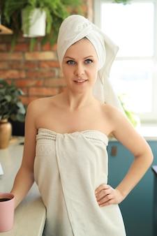 Mulher na cozinha com toalha, cobrindo o corpo depois do banho