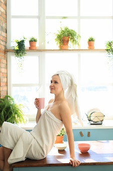 Mulher na cozinha com uma toalha na cabeça depois do banho